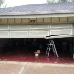 RAN INTO GARAGE DOOR WITH CAR-BROKEN BOTTOM GARAGE DOOR SECTION